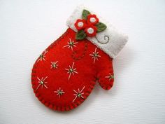 """Felt Mitten Pin By Beedeebabee @Etsy: SOLD. Here's a sweet mitten pin, done in 100% wool felt, and measuring just about 2 1\/2"""" from it's """"cuff"""" to it's tip. This little mitten, done in the perfect holiday red, has been embellished with a few holiday flowers, and a sprinkling of beaded """"twinkles""""! There is blanket stitching along it's edge and also around it's off white cuff."""