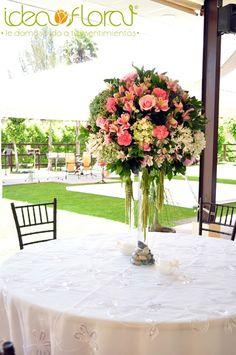 Centro de mesa alto en tonos rosa claro, blanco y verde.
