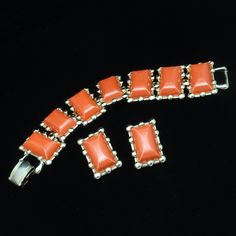 Vintage set by Coro in gold tone metal with orange thermoset plastic panels. The bracelet has a fold-over clasp; the earrings are clips. Condition is good to very good. This set is hallmarked Coro on