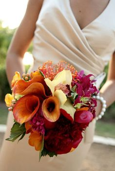 Orange, red, and yellow tropical bouquet of calla lilies, gloriosa lilies, protea pincusion, hypericum berries and cymbidium orchids