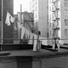 A woman hanging out the laundry on the roof of her building. Photograph by Alfred Eisenstaedt. New York City, 1939.