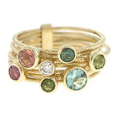 Seven 14 karat yellow gold multi-colored gemstone and diamond interconnected bands