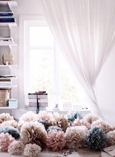 Pompones de tela sobre la cama, con colores en gama de rosados y grises. COmo si fuese una alfombra.