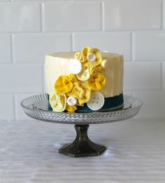 Simple buttons and fabric flower cake for a single tier. Love the monotonous color choice.