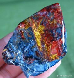 """Pietersite can have spectacular looks. This specimen is a perfect example of the vibrant swirls of reds, blues, yellows, browns, etc.Its design is what is known as """"brecciated"""", which refers to fragments of """"other stuff"""" embedded in the matrix. In the case of pietersite, it is mostly composed of hawk's eye and tiger eye.  Today, pietersite is often used to describe brecciated tiger eye.  Pietersite is a quartz based mineral with crocidolite (Na2Fe4 which is sodium and iron) plus it has…"""