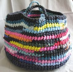 A crocheted bag with yarn from sleeves.