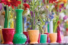 what about a collection of jewel toned vases clustered together on the small tables?