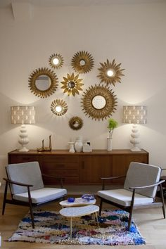 miroir sorcière oeil soleil aux rayons dorés sur un mur blanc composition de miroirs illuminés par deux lampadaires de coté