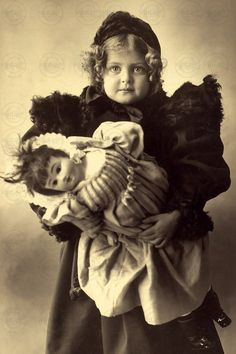 Antique photo of sweet Edwardian girl in overcoat with her doll, circa 1910.