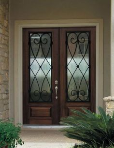 Home Entry Doors Wood. interior high dark brown wooden door with glass on the middle plus black steel curving bars plus narrow glass windows placed on the brick wall room wood glass entry doors. Awesome Front Door Design Design With Dark Brown Wood Single Double Front Entry Doors, Iron Front Door, Double Doors Exterior, Entry Doors With Glass, Wood Entry Doors, Entrance Doors, Grand Entrance, Entrance Ideas, Mediterranean Front Doors