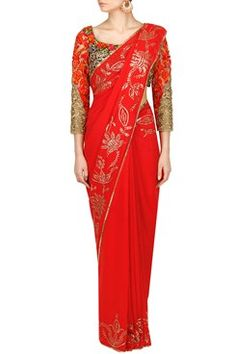 A cherry red saree based in georgette with fine metal sequins work floral embroidery on the border. It comes along with a sweetheart neckline, quarter sleeves blouse with embroidery in floral pattern and tasseled dori closure at the back. Shop this now at www.carmaonlineshop.com #carma #carmaonlineshop #indian #designer #Rimple&Harpreet #ethnic #saree #georgette #floral #wedding #embroidery #red #gold #sequins #festiveseason #shopnow