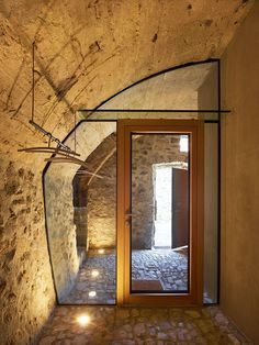"""Dramatic floor lighting on this glass wall, custom fit within the curve of a carved-out stone wall, provides simple beauty in material contrast. """"In such small spaces, it's often better to integrate the furniture and fixtures into the room,"""" says de Meuron."""