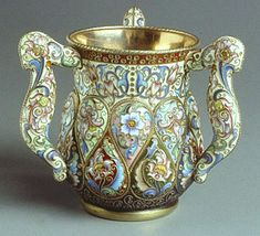 A silver-gilt and shaded cloisonné enamel three-handled loving-cup the body repoussé with pear-shaped bosses, decorated with stylized flowers, with cream ground beneath the rim and translucent purple at the base - initials of Fedor Rückert, assay mark of Moscow 1899-1908, assay master Ivan Lebedkin, inventory no. 19754, height 4 1/4 inches