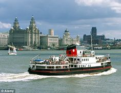 The famous Mersey ferry chugs past the 'Three Graces' lining Liverpool's waterfront