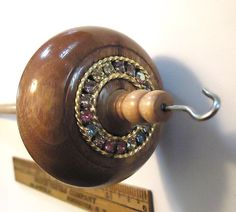Sparkly canarywood top whorl drop spindle with an antique circle pin in the top.   Sparkles in the sun. $36.00, via Etsy.