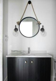 Banheiro pequeno, com espelho redondo, pia branca e gabinete preto. 🌟  Foto tirada de casa.com.br