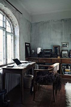 I love this studio style home office space. Although it appears to be a little dark and dreary from the concrete grey walls, the rectangular shape  wood desk and drawers bring a warmth. The white hairy area rug breaks up some the lines for softnes and light. The large windows give the room lots of natural light.