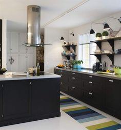 Längs ytterväggen i köket sitter en lång diskbänk i rostfritt med integrerad ho från Ett vackert kök. Matta från Pappelina. Taklampor Bestlite från Gubi.