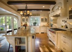 This kitchen is amazing. So many details that I love in this picture. Custom island, curved french doors, marble counters, amazing lighting. Love the custom backsplash with build in ledge above the stove! Some great ideas in this pic!