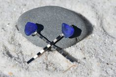 Pair of genuine surf tumbled blue sea glass hair pins. Authentic blue sea glass stones adorn delicate dainty hair pins. The hair pins are handmade and come from a smoke free environment. The hair pins measure: 51 mm x 11 mm or 1.99 inches x .44 inches  Part# 11330