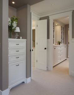 Julie Williams Design.  From the MBR, there is a walk-in closet to the right and through the door on the left is the master bath. The small piece in the foreground is a valet cabinet, which holds a charging station in the top drawer and a hamper in the bottom, with storage for scarves etc in between.