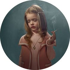 Smoking Kids: girl dressed in pink against green wall smoking cigarette.  Flemish photographer Frieke Janssens poses young children with cigarettes.