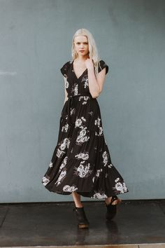 Featuring a dark floral print, this asymmetrically tiered midi dress is all things elegant and boho, featuring button closures down the back and a V-neckline. The cap sleeves have smocked shoulders. C