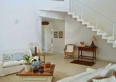 O living combina a leveza das cortinas de voil com um conjunto de sofás branco e almofadas listradas em tons de azul, evocando o espírito praiano. Mesas de apoio e aparadores em madeira completam o décor com simplicidade e descontração.