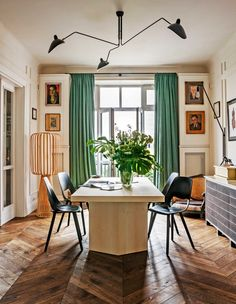 The dining room table was designed by Chrapka and her team, as were the sideboard and the steel-and-exposed-bulb lamp above it. Around the table are stained black plywood chairs from Vitra and above hangs a Serge Mouilles three-arm ceiling light. The striking floor lamp (at left) and many of the pieces of art in the room were sourced through eBay. A small French-style chair in the corner was converted into a stylish dog bed.