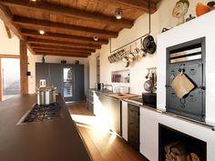 Di Bulthaup la cucina open space è attrezzatissima e ampia, illuminata dalle ampie vetrate. Lo stile minimale si trasforma a favore di un'atmosfera più rustica, da casa di campagna