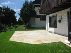 Eine sonnige Terrasse mit Sandstein Yellow Mint-Platten – jonastone
