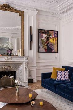 Salon moderne et contemporain avec canapé ble nuit droit avec coussin jaune curry et cheminée en marbre. On valide !