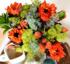 Fall is beginning to bloom with orange sunflowers, spray roses & lush greens