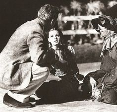 Director Victor Fleming talks with Judy Garland and Ray Bolger on the set of The Wizard of Oz, 1939