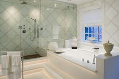 This Grecian inspired bathroom pairs perfectly with thassos marble. You'll feel like a god/godess with a walk-in glass shower and white bath tub. #beautifulbath #connecticutstone www.connecticutstone.com
