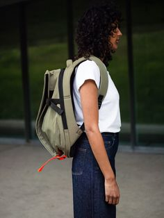 """This architectural form creates a strong silhouette that is highly practical. The asymmetrical shape features two main compartments, the front section expands according to your carrying needs. In the rear compartment, a padded pocket provides safe storage for laptops of up to 13"""". Webbing straps in complementary black and neon orange bring a touch of colour to this ISAR backpack made from a smooth Nylon and Polyester blend in khaki. World Of Fashion, New Product, Color Splash, Shoulder Strap, Pouch, Smooth, Bring It On, Backpacks, Stylish"""