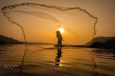 Fishermen is fishing in the river at sunrise.