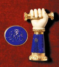 Ivory & hardstone triple desk seal with two-colour gold mounts, English, circa 1860 formed as an ivory fist wearing a small rose diamond-set ring on its little finger, clasping a baton, each end with a matrix, one of bloodstone engraved with an anchor, the other of carnelian later engraved with initials, the lapis lazuli forearm with chased leaf-tip and reeded mounts, enclosing a further lapis matrix engraved with entwined initials AR. Image Sothebys