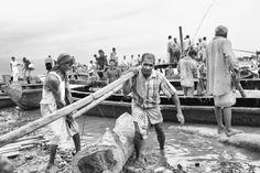 Group of Bangladeshi men lifting up timber by Pavel Gospodinov