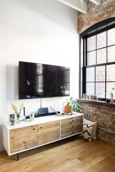 "The reclaimed wood <a href=""http://www.westelm.com/products/reclaimed-wood-lacquer-media-console-long-h1653/?pkey=cconsoles-media-storage-cabinets%7Cmedia-consoles"" target=""_blank"">credenza</a> perfectly matches the exposed beams in the other parts of the room."