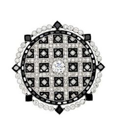 An Art Deco Onyx and Diamond Brooch, Cartier, France, circa 1915.  Of circular design, the plaque centering an old European-cut diamond, the body of grid motif with alternating patterns of onyx and smaller old European-cut diamonds diamonds, bordered by a continuous course of calibre-cut onyx and a row of diamond quartets between onyx arrows, mounted in platinum, signed Cartier