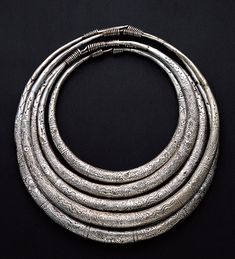 China | Silver neck rings from the Miao people | Early 20th century |  For the Miao people heavy silver neck rings are a must. This set of 5 separate closed hollow engraved neck rings are worn by both men and women. Large festive neck rings with numerous pendants are worn by the Lisu, especially on New Year's Day. The most common themes in Chinese jewellery are dragons, the phoenix, animals and plants.