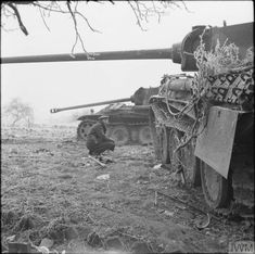 A soldier inspects two knocked-out German PzKpfw V Panther tanks near Foy-Notre-Dame, Belgium, 29 December 1944.
