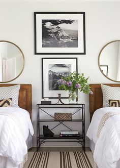 lake house bedroom features identical cognac leather beds with silver nailhead trim on twin beds dressed in soft white cotton bedding under gold convex mirrors flanking a shared nightstand, iron tiered bedside table, placed under stacked black and white photos alongside a cream and brown striped rug.