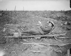 The Battle of the Somme, July-November 1916. A British soldier poses lying reading on an abandoned German stretcher. High Wood, Oct 1916. ©IWM (Q 4370)
