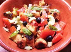 Insalata di crostini di focaccia, pomodori, cetrioli e cipolle in ciotola toscana di terracotta.