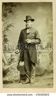 USA - ILLINOIS - CIRCA 1870 A vintage Cartes de visite photo of a man standing. He is dressed in a vest with long suit coat and bow tie wearing hat. Photo is from the Victorian era. CIRCA 1870