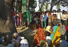 Tecavüz edilen ve öldürülerek bedenleri ağaca asılan 12 ve 14 yaşlarındaki iki kızın etrafında toplanan Hintliler.