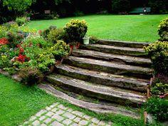 a lot of flowers around the wooden garden steps Sloped Backyard, Sloped Garden, Backyard Ideas, Garden Stairs, Terrace Garden, Garden Path, House Landscape, Landscape Design, Back Gardens