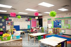 I absolutely adore this classroom. The number line wall is so adorable and the hanging flower poms with table numbers are genius.